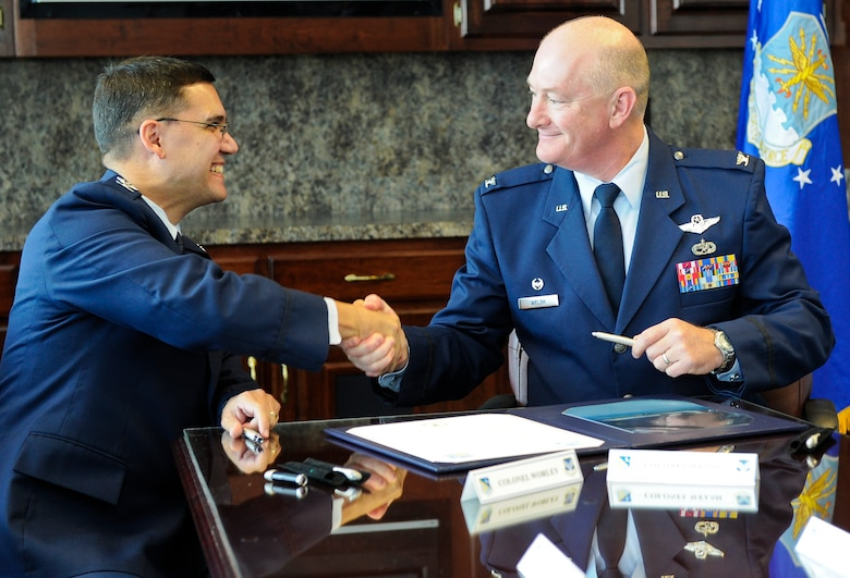 U.S. Air Force Col. L. Dean Worley Jr., left, 461st Air Control Wing commander, and Col. William Welsh, 116th Air Control Wing commander, shake hands after signing a memorandum of understanding prior to the 116th ACW Change of Command and the 461st ACW activation ceremonies at the Museum of Aviation, Robins Air Force Base, Ga., Sept. 30, 2011.  The memorandum of understanding established the initiative to optimize day-to-day operations of both wings working together as an active associate unit.  (National Guard photo by Master Sgt. Roger Parsons/Released)