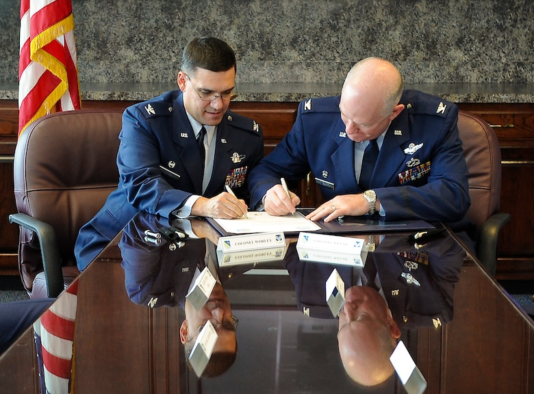 U.S. Air Force Col. L. Dean Worley Jr., left, 461st Air Control Wing commander, and Col. William Welsh, 116th Air Control Wing commander, sign a memorandum of understanding prior to the 116th ACW Change of Command and the 461st ACW activation ceremonies at the Museum of Aviation, Robins Air Force Base, Ga., Sept. 30, 2011.  The memorandum of understanding established the initiative to optimize day-to-day operations of both wings working together as an active associate unit.  (National Guard photo by Master Sgt. Roger Parsons/Released)