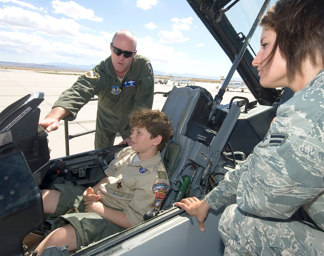Brig. Gen. Robert C. Nolan II, Air Force Flight Test Center commander, explains the workings of an F-16 to a boy scout from Troop 911 here, Oct. 1. To ensure the safety of his visitors, the commander had expert assistance from Airman 1st Class Juli Sweger, crew chief, 412th Aircraft Maintenance Squadron, and several of her teammates on the Edwards flightline. (U.S. Air Force photo by Rob Densmore)
