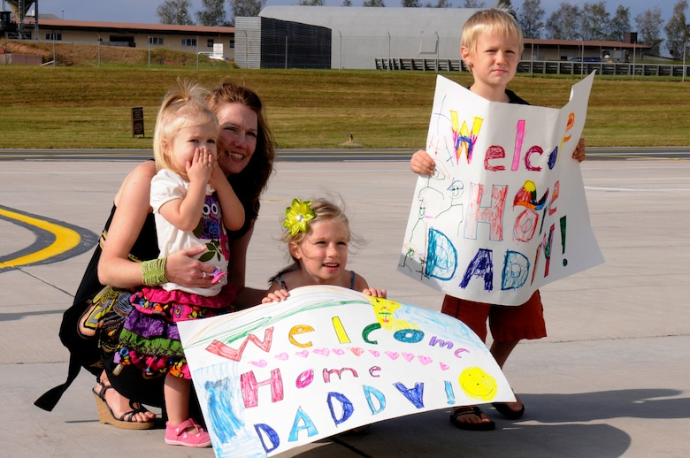 SPANGDAHLEM AIR BASE, Germany -- Bo Piepkorn, wife of Lt. Col. Aaron Piepkorn, 480th Fighter Squadron F-16 pilot, and their children (from left to right) Greta, Ella and Micah, wait for the first F-16 Fighting Falcons to land here Oct. 4. The pilots are returning from their deployment to Iraq in support of Operation New Dawn. (U.S. Air Force photo/Airman 1st Class Brittney Frees)