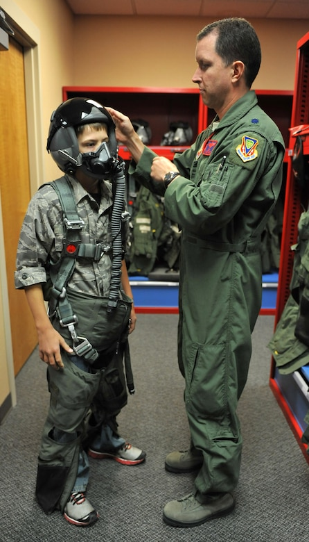 Lt. Col. Christopher Sage, 389th Fighter Squadron commander, explains to Carson McIe the importance of each part of the flight suit, Oct. 4, 2011, at Mountain Home Air Force Base, Idaho.  McIe and his parents came to Idaho to meet the troops they supported for six months while they were deployed to Afghanistan. (U.S. Air Force photo by Airman 1st Class Heather Hayward)