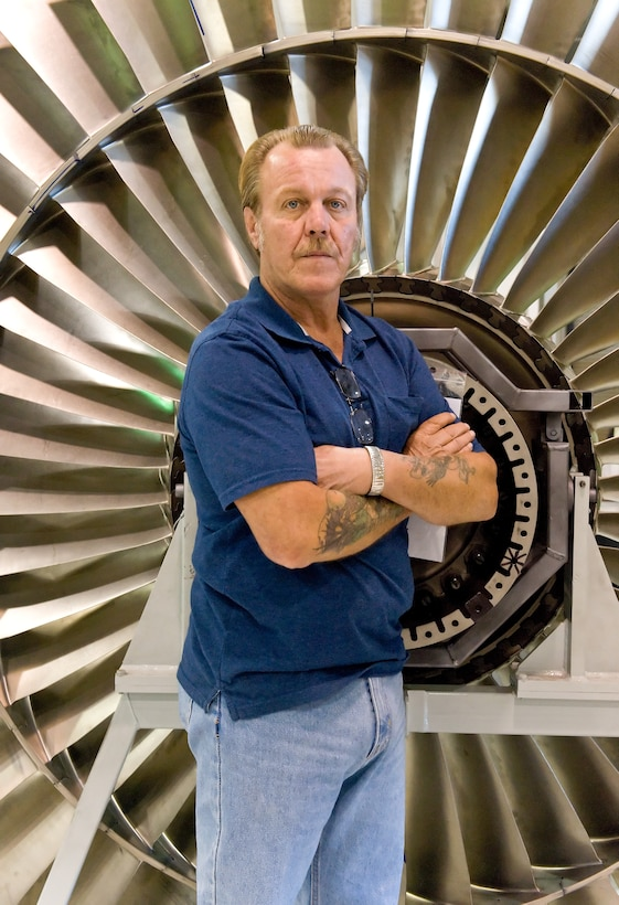 Larry Phillips, jet-engine-module-repair shop supervisor with the 436th Maintenance Squadron, stands in front of a TF-39 fan blade Oct. 6, 2011, at Dover Air Force Base, Del. Phillips has won more than $40,000 for his Innovative Development through Employee Awareness submissions, which have improved the repair process for the TF-39 engine. (U.S. Air Force photo by Roland Balik)