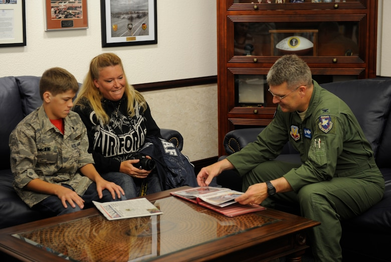 Col. Ron Buckley, 366th Fighter Wing commander, flips through a scrap book created by Angela Hoffman, mother of Carson McIe, Oct. 5, 2011, at Mountain Home Air Force Base, Idaho. Members of the 389th Aircraft Maintenance Unit flew Carson and his parents here and sponsored a base tour as a thank you for raising more than $1,000 worth of care packages during the unit's deployment. (U.S. Air Force photo by Senior Airman Angelina Drake)