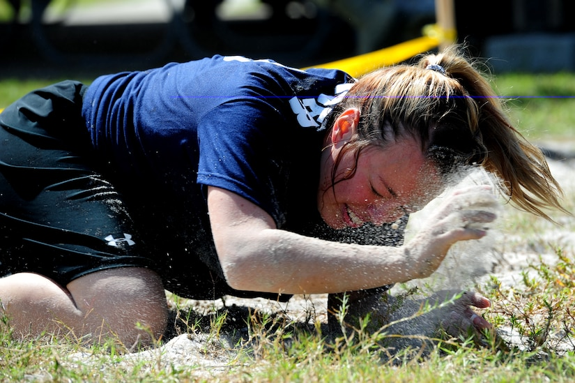 Senior Airman Amy Lexon from the Navy blue team finishes the low crawl during the team relay race at the Festival of Fitness Oct. 7, at Joint Base Charleston. Seventeen, six-man teams competed in the Festival of Fitness which included a 5k run, tug-of-war, trivia questions and a team fitness relay. The 628th Civil Engineer Squadron Lime Green Team was named the overall winner. Lexon is a Phoenix Raven with the 628th Security Forces Squadron.  (U.S. Air Force photo/ Staff Sgt. Nicole Mickle)