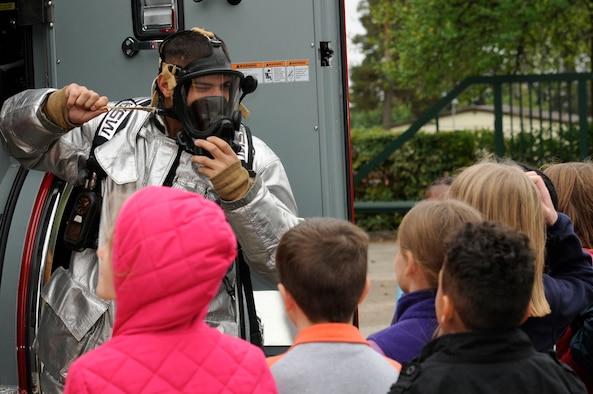 SPANGDAHLEM AIR BASE, Germany -- Airman 1st Class Spencer Quinn, 52nd Civil Engineer Squadron firefighter, shows a gas mask to children from the Spangdahlem Elementary School during a fire safety demonstration here Oct. 12. National Fire Prevention Week is a week-long schedule of events that promotes fire safety and prevention through demos, visits from Sparky the Fire Dog and a parade in Spangdahlem housing. (U.S. Air Force photo/Airman 1st Class Brittney Frees)