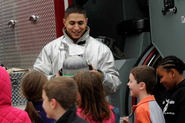 SPANGDAHLEM AIR BASE, Germany -- Airman 1st Class Spencer Quinn, 52nd Civil Engineer Squadron firefighter, shows an oxygen tank to children from the Spangdahlem Elementary School during a fire safety demonstration here Oct. 12. National Fire Prevention Week is a week-long schedule of events that promotes fire safety and prevention through demos, visits from Sparky the Fire Dog and a parade in Spangdahlem housing. (U.S. Air Force photo/Airman 1st Class Brittney Frees)