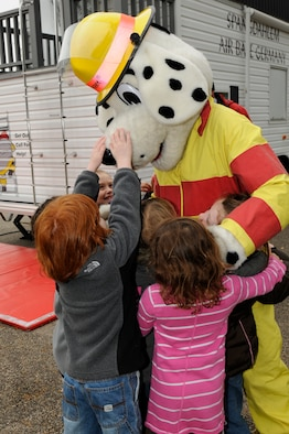 SPANGDAHLEM AIR BASE, Germany -- Sparky the Fire Dog hugs children from the Spangdahlem Elementary School during a fire safety demonstration here Oct. 12. National Fire Prevention Week is a week-long schedule of events that promotes fire safety and prevention through demos, visits from Sparky the Fire Dog and a parade in Spangdahlem housing. (U.S. Air Force photo/Airman 1st Class Brittney Frees)