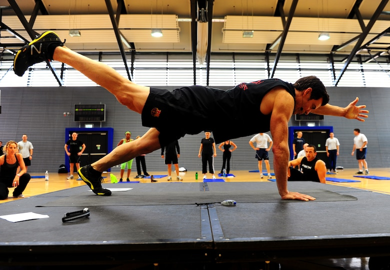 Tony Horton, creator of workout program P90X, demontrates an excercise during a calisthenics routine at the southside gym, Ramstein Air Base, Germany, Oct. 7, 2011. Horton conducted two free strength training workout sessions for 325 military personnel and dependents. (U.S. Air Force photo by Airman 1st Class Brea Miller)