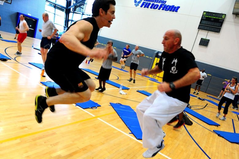 Tony Horton, creator of workout program P90X, motivates Paul Wagner, 886th Civil Engineer Squadron fire inspector, during a calisthenics routine at the southside gym, Ramstein Air Base, Germany, Oct. 7, 2011. Horton conducted two free strength training workout sessions for 325 military personnel and dependents. (U.S. Air Force photo by Airman 1st Class Brea Miller)