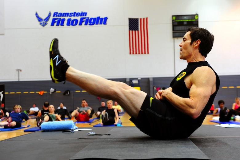 Tony Horton, creator of workout program P90X, leads an abdominal excercise during a calisthenics routine at the southside gym, Ramstein Air Base, Germany, Oct. 7, 2011. Horton conducted two free strength training workout sessions for 325 military personnel and dependents. (U.S. Air Force photo by Airman 1st Class Brea Miller)