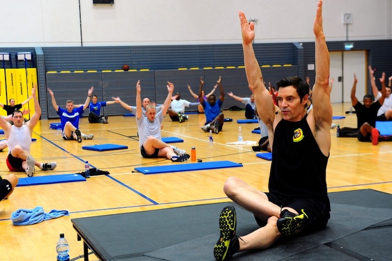 Tony Horton, creator of workout program P90X, leads a warm-up stretch before a calisthenics routine at the southside gym, Ramstein Air Base, Germany, Oct. 7, 2011. Horton conducted two free strength training workout sessions for 325 military personnel and dependents. (U.S. Air Force photo by Airman 1st Class Brea Miller)