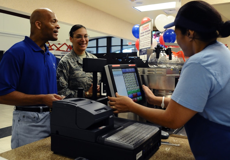 ANDERSEN AIR FORCE BASE, Guam—Chief Master Sgt. Margarita Overton, 36th Wing command chief, orders coffee with her husband, Mark during the grand opening of the Duncan Donuts coffee shop here, Oct. 14. The Army and Air Force Exchange Service (AAFES) put in the new store to improve the quality of life for Airmen at Andersen. (U.S. Air Force photo by Senior Airman Benjamin Wiseman/Released)