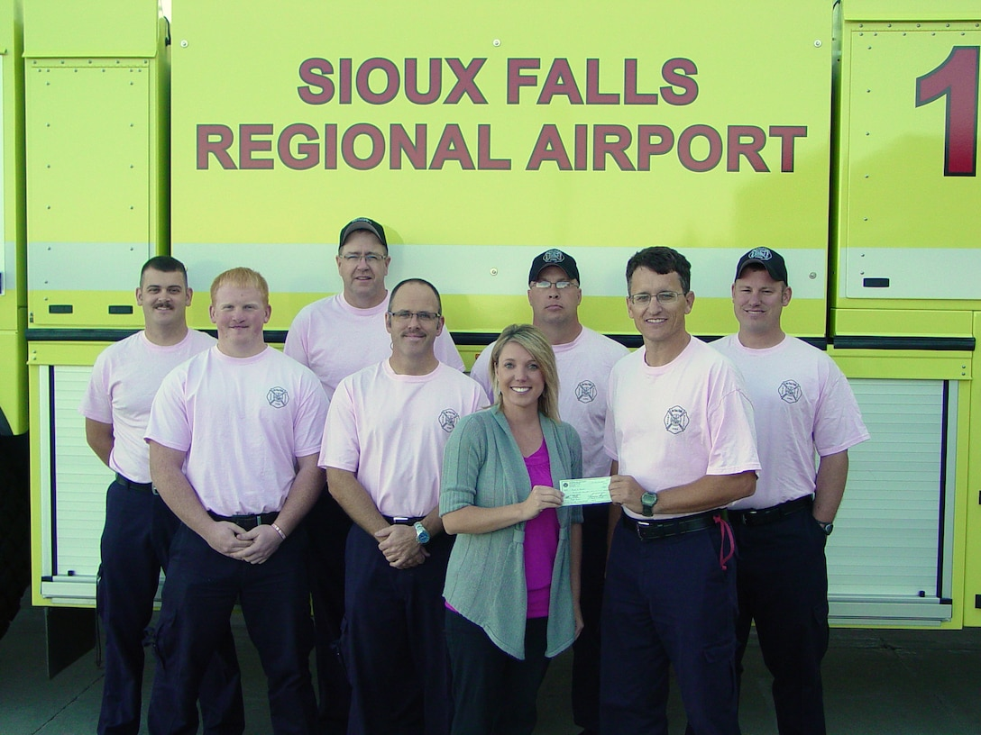 SIOUX FALLS, S.D. - Members of the B shift of the Crash, Fire, Rescue station at Joe Foss Field present a check for 600 dollars to Amanda Anderson, South Dakota Executive Director of the Susan G. Komen Foundation, on behalf of all the firefighters at the station October 13, 2011.  Firefighters at the station raised funds to support the foundation during the month of October which is Breast Cancer Awareness month as well as Fire Prevention month. (National Guard photo by Master Sgt. Thomas Krier)(RELEASED)