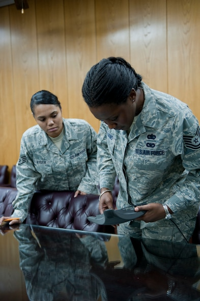 Tech. Sgt. Lakiesha Williams, right, and Staff Sgt. Vanessa Kyota, both 39th Mission Support Group knowledge operations management technicians, inspect a teleconference microphone receiver Oct. 11, 2011, at Incirlik Air Base, Turkey. KOMT members are the liaisons between the Client Systems Team and the 39th MSG staff members for creating and ensuring completion of communications related trouble tickets. (U.S. Air Force photo by Senior Airman Anthony Sanchelli/Released)