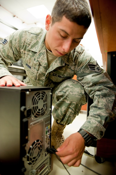 Senior Airman Brian Janik, 39th Communications Squadron client systems technician, plugs a mouse and keyboard into a computer that needs system updates Oct. 11, 2011, at Incirlik Air Base, Turkey. The Client Systems Team provides system updates to nearly 1,800 network computers at Incirlik. (U.S. Air Force photo by Senior Airman Anthony Sanchelli/Released)