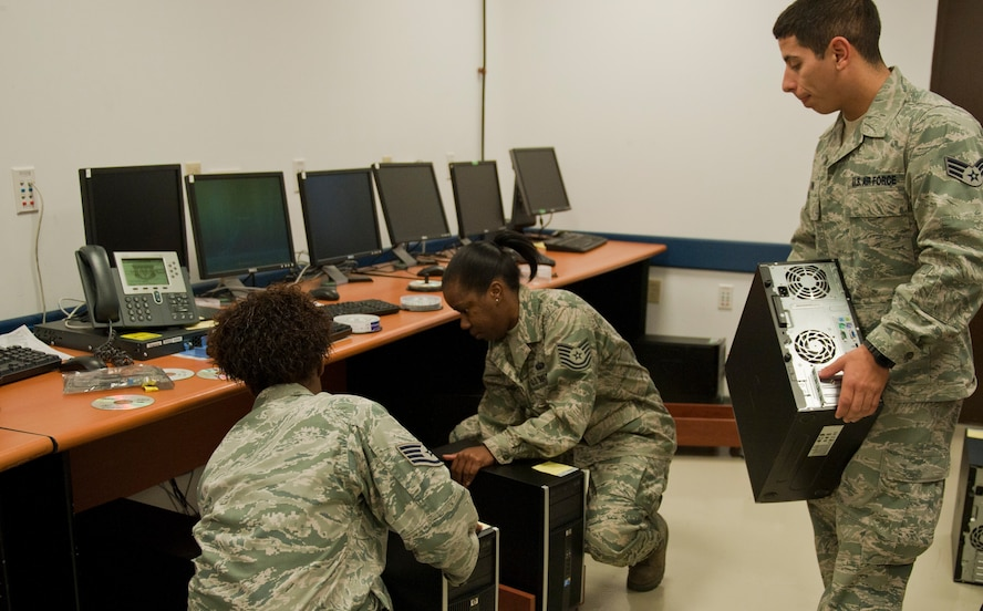 Staff Sgt. Jasmine Rhodes, 39th Communications Squadron client systems technician, left, and Tech. Sgt. Kaneel Williams, 39th CS Client Systems Team NCO in charge, plug in computers that need system updates, while Senior Airman Brian Janik, 39th CS client systems technician, brings in an additional computer Oct. 11, 2011, at Incirlik Air Base, Turkey. The CST provides system updates to nearly 1,800 network computers at Incirlik. (U.S. Air Force photo by Senior Airman Anthony Sanchelli/Released)
