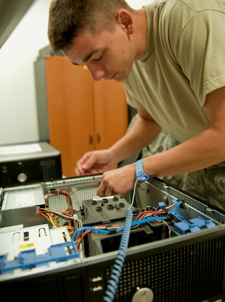 Airman 1st Class Mike Hareld, 39th Communications Squadron base equipment control officer, removes a faulty video card from a computer Oct. 11, 2011, at Incirlik Air Base, Turkey. As part of his equipment control duties, Hareld ensures computers are working properly before being used by units on base. (U.S. Air Force photo by Senior Airman Anthony Sanchelli/Released)