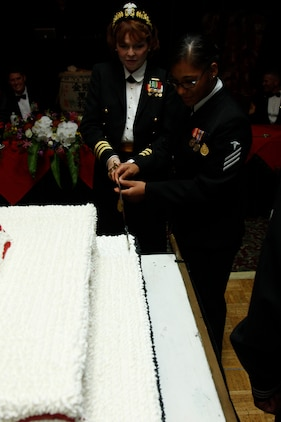 Cmdr. Sheri Coleman and Seaman Apprentice Estephani Torres, the oldest and youngest sailors in attendance, both cut the first slice of cake during the 2011 Navy Ball at the Club Iwakuni ballroom here Oct. 14. As is tradition, Coleman handed the piece to Torres to take the first bite.