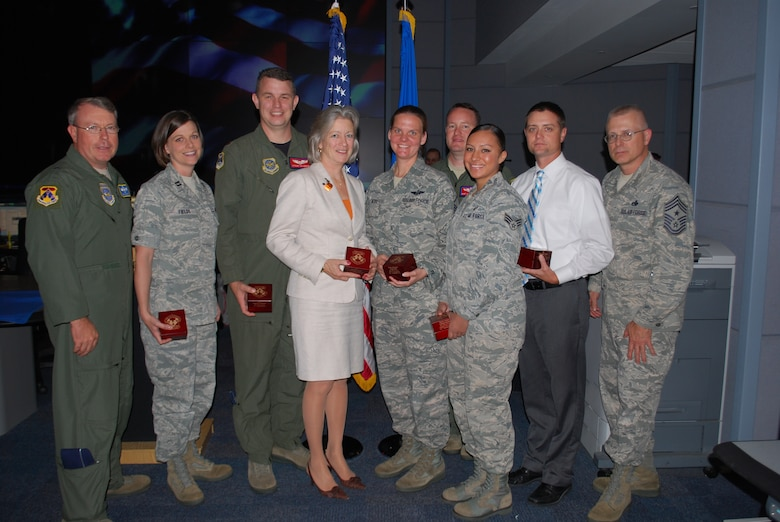 18th Air Force Vice Commander Brig Gen. Bryan Benson (far left) and18th Air Force Command Chief Chief Master Sgt. Jeffrey Williams (far right), with winners of the Headquarters, 18th Air Force Third Quarter Awards here Oct. 13. From left to right: Capt. Cynthia Fields (Company Grade Officer of the Quarter), Maj. Anthony Calabrese (Field Grade Officer of the Quarter), Barbara Jacob (Civilian of the Quarter, Category III), Master Sgt. Emily Noel (Senior NCO of the Quarter), Tech Sgt. Jason Schaub (NCO of the Quarter), Senior Airman Nathalia Robles (Junior Enlisted Member of the Quarter), and Christopher Wren (Civilian of the Quarter, Category II). (U.S. Air Force Photo by 1st Lt. Marshel Slater/Released.)