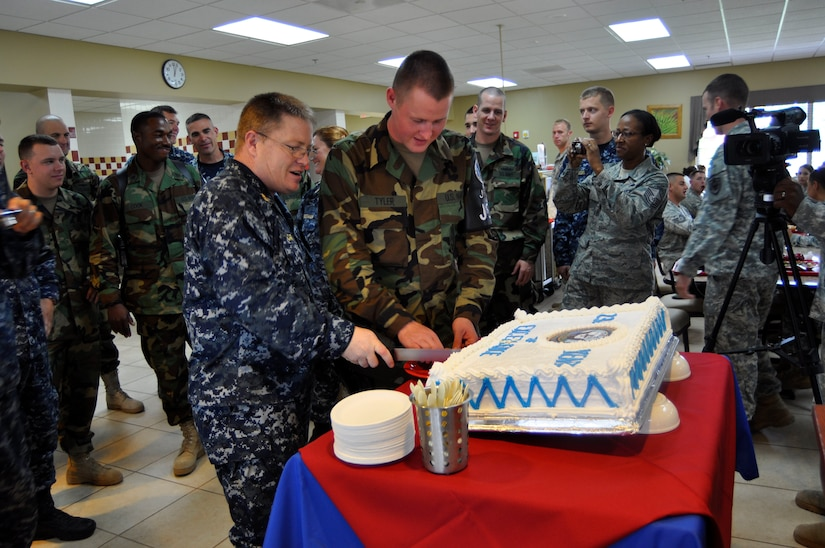 Senior Chief Petty Officer Edwin Carr, the oldest sailor assigned to Joint Task Force-Bravo, cuts the cake with the youngest sailor, Master at Arms Seaman Dustin Tyler, celebrating the Navy's Birthday in the dining facility Oct. 13, 2011, at Soto Cano Air Base, Honduras.  JTF-Bravo sailors honored the Navy's 236th birthday with the traditional cutting of the cake. (U.S. Air Force photo/Martin Chahin)