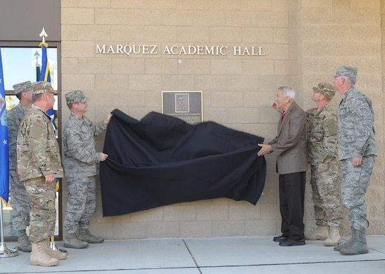 (Left) Col. Phillip Stewart, 9th Reconnaissance Wing vice commander, assists (right) retired Lt. Gen. Leo Marquez, founder of the Air Force Combat Ammunition School, unveil the dedication plaque of the school's main building renaming it to Marquez Academic Hall. The dedication was part of AFCOMAC's 25th Anniversary celebration. (U.S. Air Force photo by Mr. John Schwab)