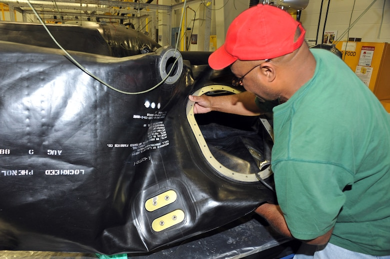 Lyndon Baines Johnson, 402nd Commodities Maintenance Group Fuel Cell Repair Shop mechanic, inspects a fuel cell bladder. Johnson came up with a new process of repairing and replacing the bladders which helped solve an OSHA citation. U.S. Air Force file photo by Tommie Horton