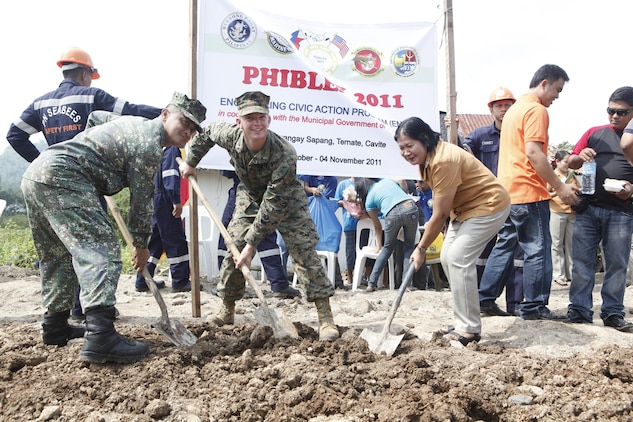 Nestor Soler, Philippine marine corps major, left, 1st Lt. Ian Dick, middle, and Marietta Bengo, right, principal of Sapang Elementary School pose after breaking ground at the opening ceremony for the new school being built in Ternate, Republic of the Philippines, Oct. 6. The school is being built as part of Amphibious Landing Exercise 2012. Phiblex '12 is an annual bilateral training exercise held between AFP and U.S. Military personnel and is designed to improve interoperability, combat readiness and enhance security cooperation throughout the region. Dick is with Marine Wing Support Squadron 171, Marine Aircraft Group 36, 3rd Marine Expeditionary Brigade, III Marine Expeditionary Force.