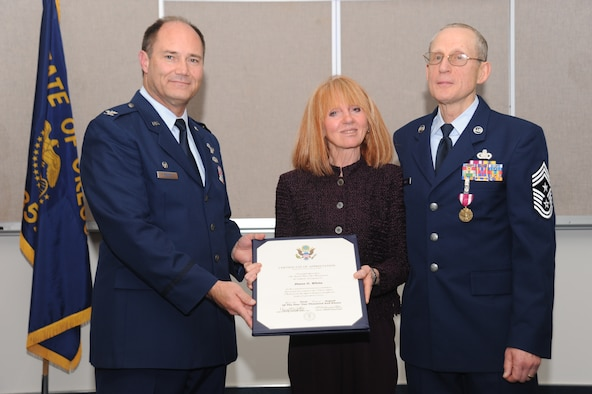 PORTLAND, Ore. - Diane White, Command Chief Max White's wife, received a certificate of appreciation from Col. Michael Stencel, 142d Fighter Wing Commander. The presentation was at Command Chief Max White's retirement ceremony October 16.(Air Force photo taken by Tech. Sgt John Hughel)