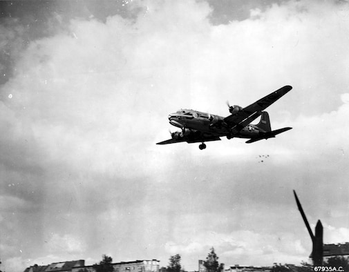 "A ""Little Vittles"" candy drop. Note the parachutes below the tail of the C-54. (U.S. Air Force photo)"