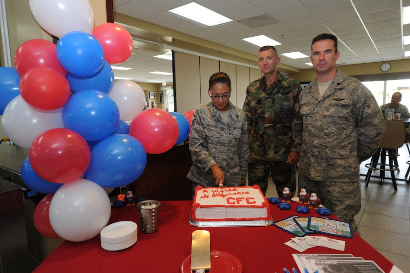 Master Sgt. Yvonne Espinosa, Joint Task Force-Bravo CFC coordinator, cuts a cake to celebrate the beginning of the Combined Federal Campaign with Lt. Col. Eric Moses, 612th ABS commander and Lt. Col. Christopher Buckley, JTF-Bravo chief of staff, Oct. 17, 2011, at Soto Cano Air Base, Honduras. (U.S. Air Force photo/Tech. Sgt Matthew McGovern)