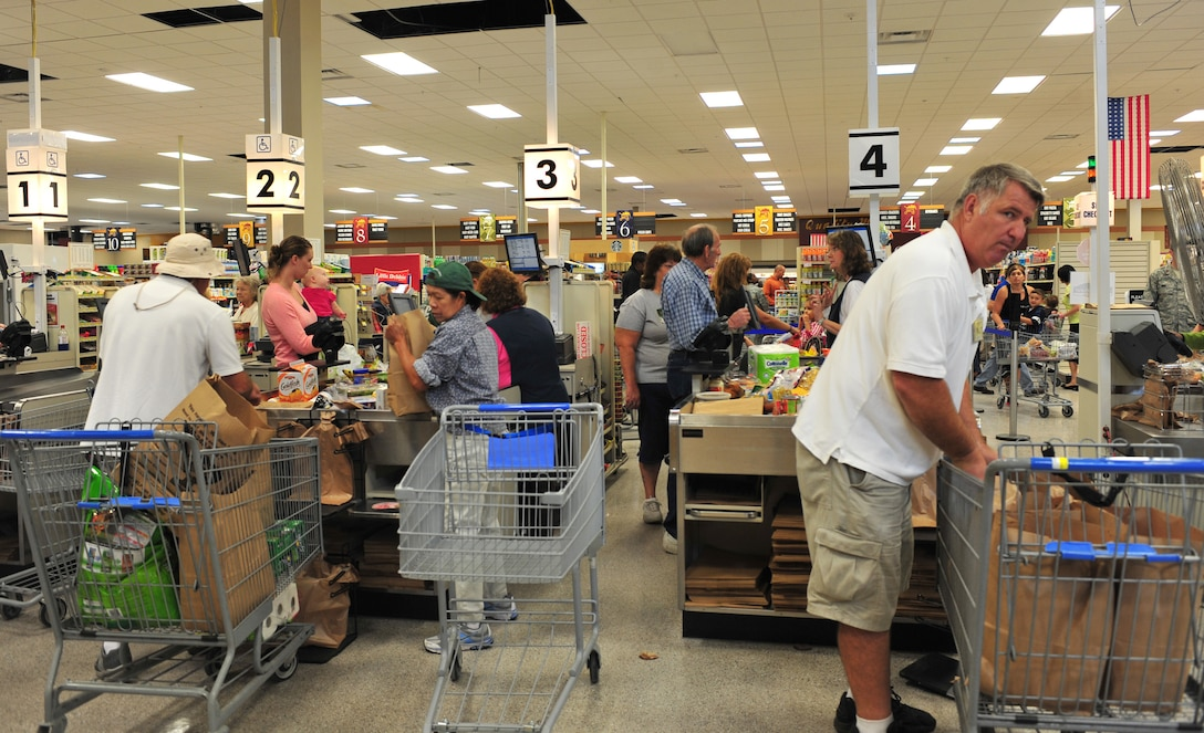 Commissary cashiers and baggers process shoppers through the checkout line during the reopening at Moody Air Force Base, Ga., Oct. 19, 2011. The commissary will be adding new registers and start utilizing new electric shelf labels within the next few months to help save money and man hours. All of the renovations, new equipment and labor were paid for by the surcharges applied during checkout. (U.S. Air Force photo by Staff Sgt. Stephanie Mancha/Released)