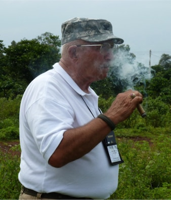 Air Force Reserve Command's 34th Aeromedical Evacuation Squadron, Peterson Air Force Base, Colo. Honorary Commander retired Army Col. Bill McPherson, smokes a cigar in remembrance of his comrade, 22-year-old co-pilot, CW2 John Grow. After 45 years the colonel returned to his Huey gunship crash site in Vietnam that took the life of his co-pilot and left him with multiple gunshot scars. (Courtesy photo)