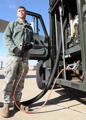 "U.S. Air Force Senior Airman Tanner Dalton, 27th Special Operations Logistics Readiness Squadron fuels apprentice, grips a hose, also called a ""dead man"" hose, used to initiate and halt refueling of aircraft on the flightline at Cannon Air Force Base, N.M., Oct. 18, 2011. The refueling process varies in time depending on the load capacity of the aircraft in need of service.  (U.S. Air Force photo by Airman 1st Class Alexxis Pons Abascal)"