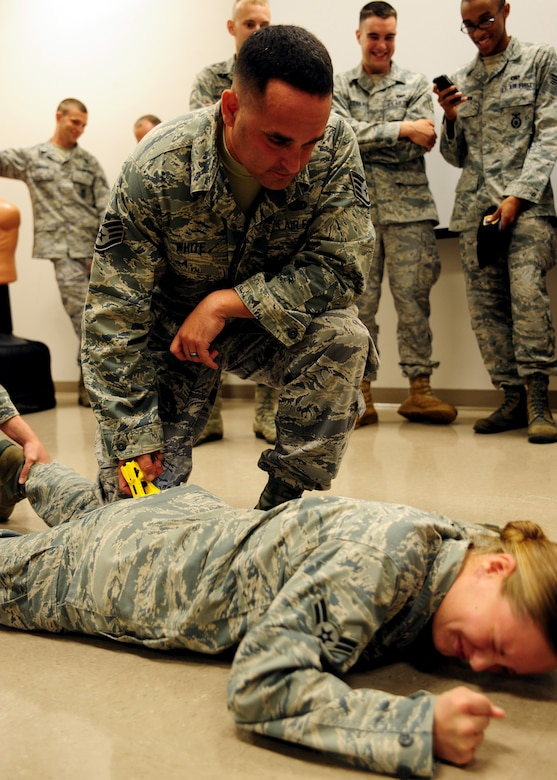 Airman 1st Class Heather Ives reacts to being tased by Staff Sgt. Neil White after volunteering to be tased at Joint Base Charleston Oct. 18. The taser is a preventive measure and often prevents unnecessary loss of life. Both White, a Security Forces Trainer and  Ives, a Security Forces Apprentice, are with the 628th Security Forces Squadron. (U.S. Air Force photo/Staff Sgt. Katie Gieratz)
