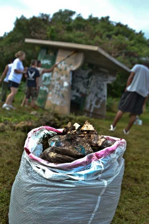 Airmen from the 36th Maintenance Squadron, 36th Wing chapel and their families pick up debris and trash prior to painting a bus stop for an Island Beautification project in Mangilao, Guam Oct 15.  Throughout the year, squadrons from Andersen AFB volunteer their time to help clean, repair and build areas in Guam communities in support of the Islandwide Beautification Task Force. (U.S. Air Force photo by Staff Sgt. Alexandre Montes/RELEASED)