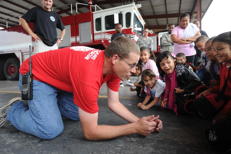 Tech. Sgt. Joseph Nix, 612th ABS assistance chief of fire prevention, teaches local kindergarten children to stay low when encountering smoke Oct. 19, 2011, at Soto Cano Air Base, Honduras. Airmen from the 612th Air Base Squadron's fire department provided fire safety training to more than 95 local kindergarten children during fire prevention week. (U.S. Air Force photo/Tech.Sgt. Matthew McGovern)