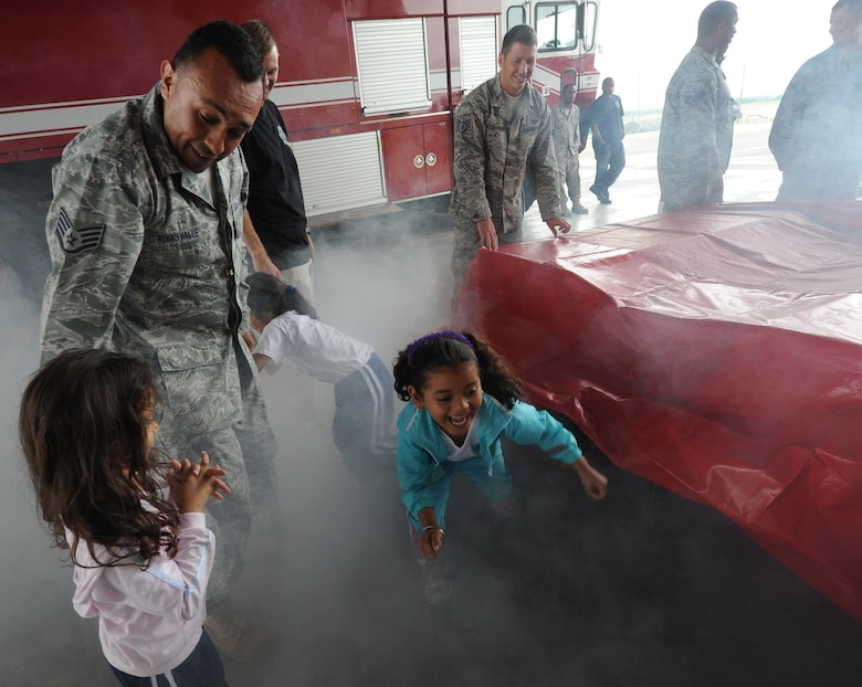 Airmen from the 612th Air Base Squadron's fire department help children crawl through a simulator containing dry ice smoke as part of fire safety training Oct. 19, 2011, at Soto Cano Air Base, Honduras. Other activities included a smoke detector class, fire station tour and water truck demonstration. (U.S. Air Force photo/Tech. Sgt. Matthew McGovern)