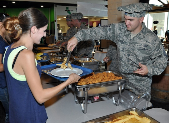 Master Sgt. Andrew Flora, 9th Maintenance Operations Squadron first sergeant, serves food to a spouse of a deployed Airman during the Hearts Apart Dinner at the Contrails Inn Dinning Facility Oct. 13. The pirate themed dinner and was hosted by the Airman and Family Readiness Center together with Beale's first sergeants. (U.S. Air Force photo by Airman 1st Class Shawn Nickel)