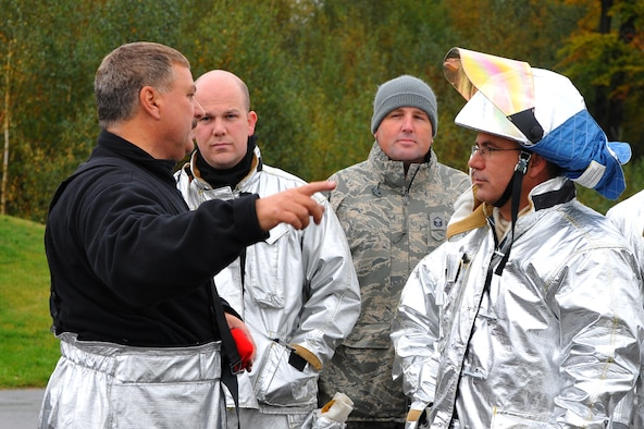 RAMSTEIN AIR BASE, Germany – Dieter Bestyak, left, 886th Civil Engineer Squadron Fire Protection Flight training officer, briefs firefighters from the 52nd CES before live fire training here Oct. 19. Live fire training is mandatory for firefighters to complete twice a year. The training ensures firefighters are able to perform required core tasks in the event of an aircraft fire to protect lives and U.S. government assets. (U.S. Air Force photo/Airman 1st Class Dillon Davis)