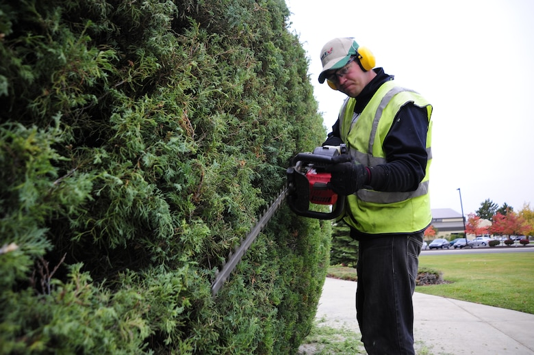 Adam Joseph Tomcho, Skils'kin grounds maintenance worker, uses a hedge trimmer to trim a bush in front of the Military Personnel Flight building Oct. 14. Adam has been with Skils'kin for three years and says that it has been good for him working with the company. (U.S. Air Force photo/Airman 1st Class Taylor Curry)