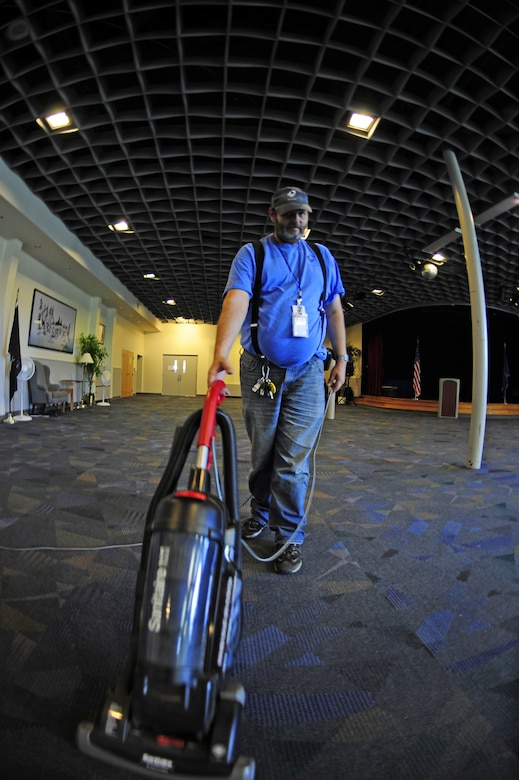 Edgar Schmidt, Skils'kin janitorial custodian, vacuums the floor in the ballroom at the Deel Community Center Oct. 13. Edgar has been an employee for Skils'kin for 13 years. He used to work for the grounds section of the company and said it is fun and very interesting. (U.S. Air Force photo/Airman 1st Class Taylor Curry)