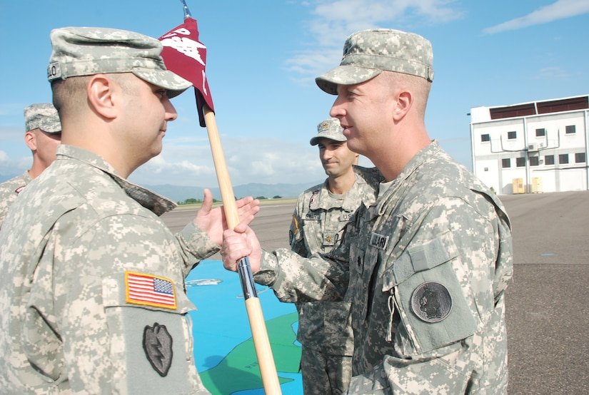 Capt. Mike Crivello, C Company commander of the 1st Battalion 228th Regiment, receives the company's guidon from Lt. Col. Michael Breslin, commander of the 1st Battalion, 228th Aviation Regiment during a change of command ceremony Oct. 21, 2011 at Soto Cano Air Base, Honduras. Maj. Seth Swartz, outgoing C Company commander, takes part in the ceremony. (U.S. Air Force photo/Capt. Candice Allen)