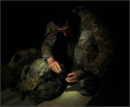 U.S. Marine Sergeant Christopher Bickel, Marine Air Traffic Control Mobile Team assistant team leader, 22nd Marine Expeditionary Unit, prepares his night vision goggles before checking the alignment of phantom lights on an austere landing zone at Chabelley Airfield, Djibouti, October 21. Bickel is originally from Lima, Ohio. He is part of a team that sets up ALZs, which allow aircraft such as C-130 Hercules and C-17 Globemaster III cargo transport aircraft to land anywhere in the world, day or night.