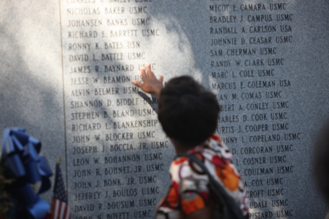 A Beirut Memorial Observance Ceremony attendee finds a name of a Marine, who lost his life in the Beirut bombing at Marine barracks, in Beirut, Lebanon at the Beirut Memorial wall at the Lejeune Memorial Gardens in Jacksonville, N.C., Oct. 23. The bombings killed 241 Marines, sailors and soldiers on Oct. 23, 1983.