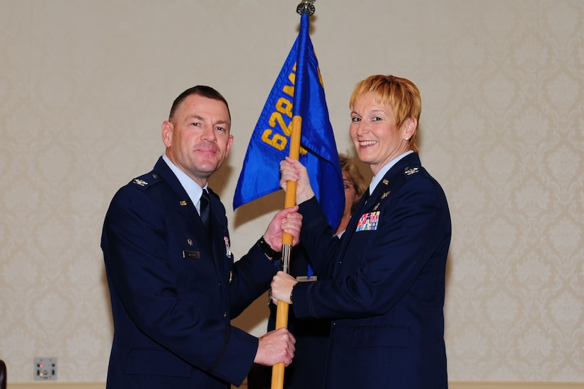 Col. Judith Hughes accepts the 628th Medical Group guidon from Col. Richard McComb during the 628th MDG change of command Oct. 21 at Joint Base Charleston. Hughes is the new 628th MDG commander and McComb is the Joint Base Charleston commander. (U.S. Air Force photo/Tech. Sgt. Chrissy Best)