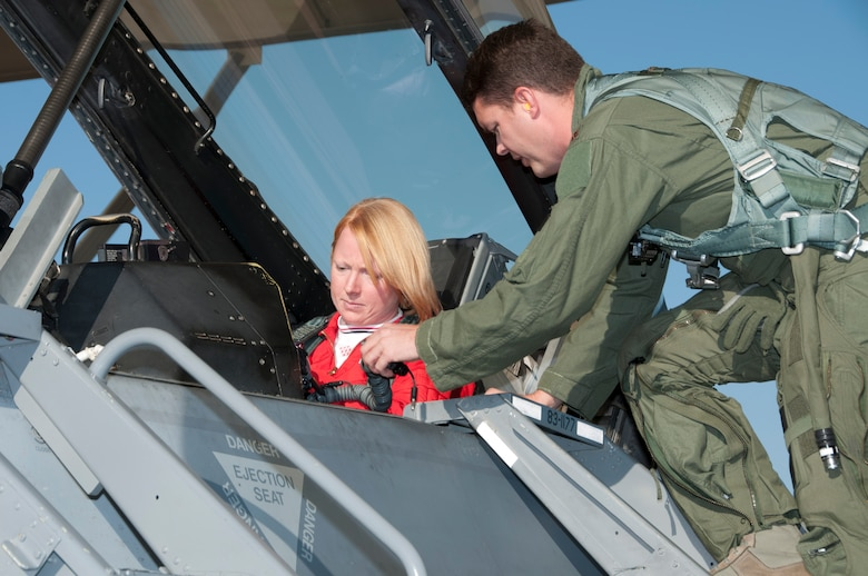 Maj. John Smith, an instructor pilot at the 162nd Fighter Wing, ensures RAF Flight Lt. Kirsty Stewart is ready to fly in an F-16 Fighting Falcon at Tucson International Airport, Oct. 21. (U.S. Air Force photo/Master Sgt. Dave Neve)