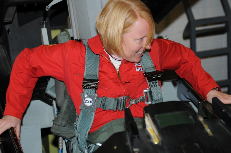RAF Flight Lt. Kirsty Stewart climbs into an F-16 egress trainer, Oct. 20. Stewart, a member of the United Kingdom's Red Arrows aerial demonstration team, flew with the international F-16 training wing, Oct. 21. (U.S. Air Force photo/Maj. Gabe Johnson)