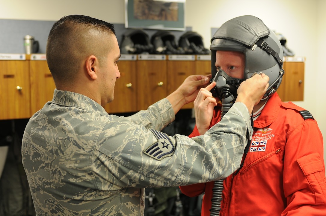 Staff Sgt. Luis Aguilar fits RAF Flight Lt. Kirsty Stewart with a helmet and oxygen mask in preparation for her F-16 orientation flight at the 162nd Fighter Wing at Tucson International Airport. Stewart, a member of the United Kingdom's Red Arrows aerial demonstration team, flew with the international F-16 training wing, Oct. 21.  (U.S. Air Force photo/Maj. Gabe Johnson)