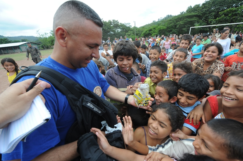 Master Sgt. Josue Guzman, from Joint Task Force-Bravo ports and planning, hands out candy to children of El Sitio Oct. 22, 2011, near Soto Cano Air Base, Honduras. Nearly 150 Joint Task Force-Bravo personnel hiked three miles to deliver food to the small village. (U.S. Air Force photo/Tech. Sgt. Matthew McGovern)
