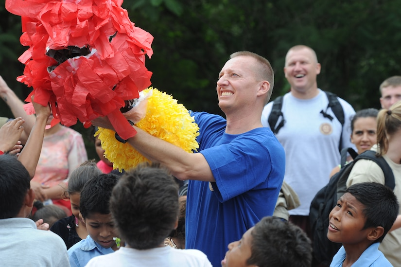 Chaplain (Capt.) Mark Williams, JTF-Bravo Command Chaplain, shakes the remaining candy out of a pinata Oct. 22, 2011 at El Sitio, near Soto Cano Air Base, Honduras. Nearly 150 Joint Task Force-Bravo personnel hiked three miles to deliver food to the small village. (U.S. Air Force photo/Tech. Sgt. Matthew McGovern)